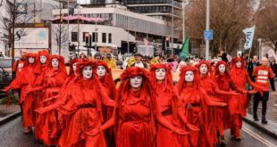 Red rebels witnessing the protest against the proposed airport expansion in Bris...